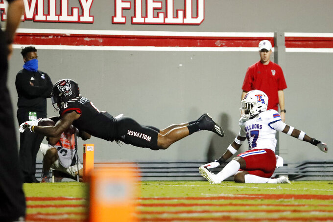 North Carolina State's Ricky Person Jr. (8) breaks away from the tackle of Louisiana Tech's Brodrick Calhoun (17) to score during the first half of an NCAA college football game in Raleigh, N.C., Saturday, Oct. 2, 2021. (AP Photo/Karl B DeBlaker)