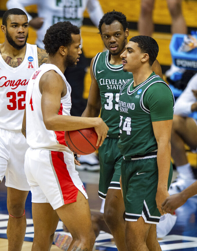 Houston forward Justin Gorham, left, and Cleveland State guard Torrey Patton, right, stare at one another after a tense battle for the ball during the first half of a first-round game in the NCAA men's college basketball tournament, Friday, March 19, 2021, at Assembly Hall in Bloomington, Ind. (AP Photo/Doug McSchooler)