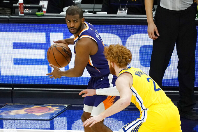 Phoenix Suns guard Chris Paul is defended by Golden State Warriors guard Nico Mannion during the second half of an NBA basketball game Thursday, March 4, 2021, in Phoenix. (AP Photo/Rick Scuteri)