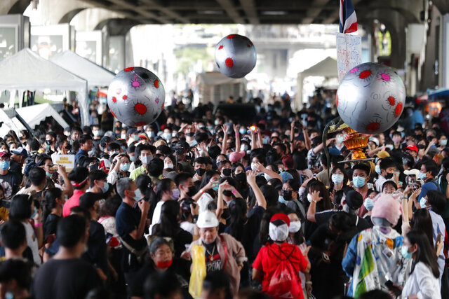 Large balls that depict asteroids are thrown in the air over a crowd attending a student rally in Bangkok, Saturday, Nov. 21, 2020. Organized by a group that mockingly calls themselves