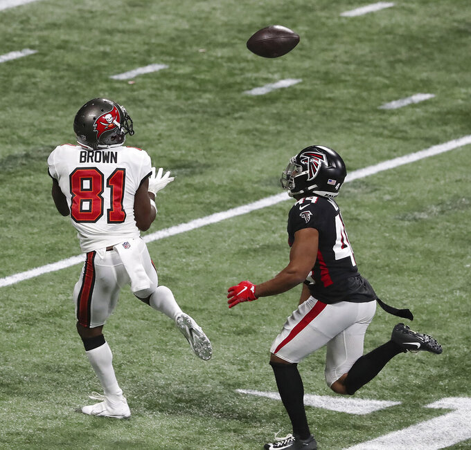 Tampa Bay Buccaneers wide receiver Antonio Brown, left, gets past Atlanta Falcons cornerback Tyler Hall for what proved to be the winning touchdown in the final minutes of an NFL football game Sunday, Dec. 20, 2020, in Atlanta. (Curtis Compton/Atlanta Journal-Constitution via AP)