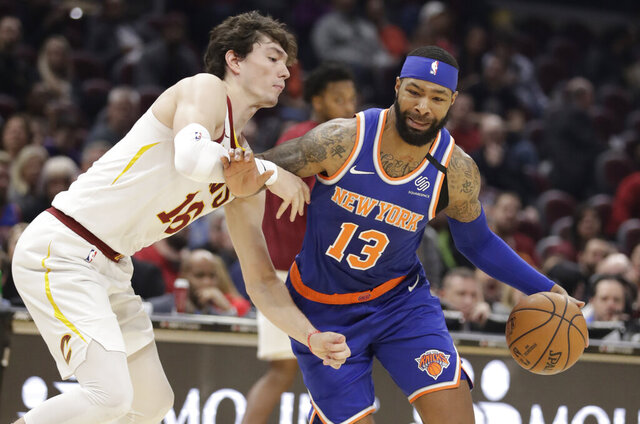 New York Knicks' Marcus Morris Sr. (13) drives to the basket against Cleveland Cavaliers' Cedi Osman (16) in the second half of an NBA basketball game, Monday, Feb. 3, 2020, in Cleveland. New York won 139-134 in overtime. (AP Photo/Tony Dejak)