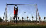 Antonio Velasquez, a pastor and director of the Maya Chapin soccer league of over 108 teams, prepares goal netting prior to several games Wednesday, April 17, 2019, in Phoenix. (AP Photo/Ross D. Franklin)