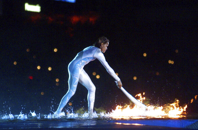 FILE - In this Sept. 15, 2000, file photo, Australian Olympic athlete Cathy Freeman ignites the Olympic flame during the opening ceremony for the Summer Olympics at Olympic Stadium in Sydney. Freeman ignited the cauldron to open the first games of the millennium and lit up Sydney Olympic Stadium 10 nights later by winning an era-defining gold medal for Australia. (AP Photo/Victoria Arocho, File)