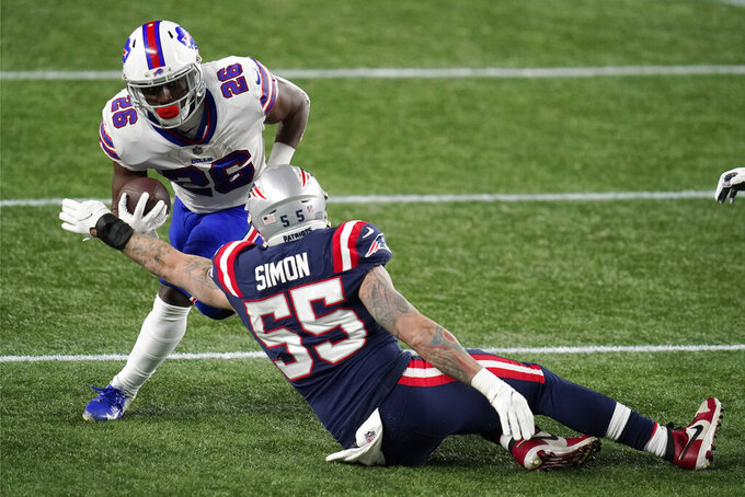 Buffalo Bills running back Devin Singletary (26) carries the ball as New England Patriots defensive end John Simon tries to stop him in the first half of an NFL football game, Monday, Dec. 28, 2020, in Foxborough, Mass. (AP Photo/Charles Krupa)