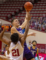 Northwestern forward Miller Kopp (10) shoots next to Indiana forward Jerome Hunter (21) during the first half of an NCAA college basketball game Wednesday, Dec. 23, 2020, in Bloomington, Ind. (AP Photo/Doug McSchooler)