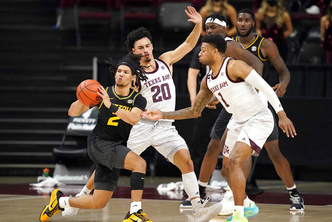Missouri guard Drew Buggs (2) looks to pass against Texas A&M guard Savion Flagg (1) and guard Andre Gordon (20) during the second half of an NCAA college basketball game Saturday, Jan. 16, 2021, in College Station, Texas. (AP Photo/Sam Craft)