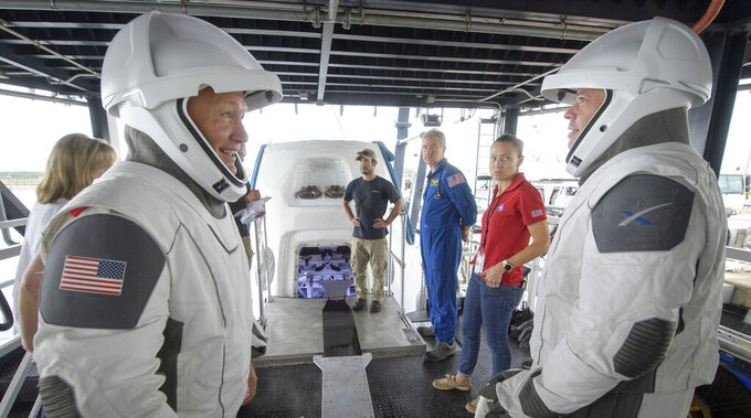 FILE - In this Aug. 13, 2019, file photo, NASA astronauts Doug Hurley, left, and Bob Behnken work with teams from NASA and SpaceX to rehearse crew extraction from SpaceX's Crew Dragon, which will be used to carry humans to the International Space Station, at the Trident Basin in Cape Canaveral, Fla. For the first time in nearly a decade, the two astronauts blasted towards orbit aboard an American rocket from American soil on May 30 2020, a first for a private company. (Bill Ingalls/NASA via AP, File)