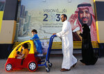 In this Wednesday, Feb. 5, 2020, photo, people walk past a banner showing Saudi Crown Prince Mohammed bin Salman, outside a mall in Jiddah, Saudi Arabia. Human rights organization Amnesty International says Saudi Arabia has used a special anti-terrorism court as