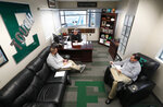 Eastern Michigan football coach Chris Creighton talks with Dylan Saccade, left, Director of Football Operations and Greg Steiner, right, Associate Athletic Director for Athletic Media Relations about logistics for the teams NCAA football game in the Camellia Bowl in Ypsilanti, Mich., Monday, Dec. 10, 2018. The Eagles will face Georgia Southern in the Camellia Bowl on Saturday, earning a spot in NCAA football postseason play for the second time in three years and just the third time in school history. (AP Photo/Paul Sancya)