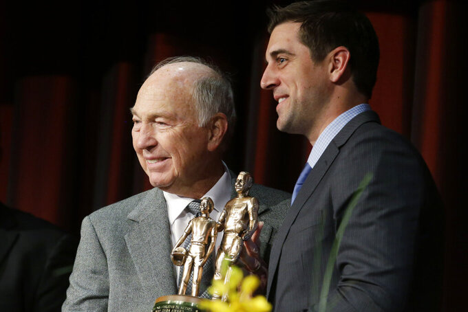 FILE - In this Jan. 31, 2014, file photo, legendary Green Bay Packers quarterback Bart Starr, left, presents current Packers quarterback Aaron Rogers, right, with the the Bart Starr Award for Character and Leadership at the Super Bowl Breakfast in New York. When Roger's stock took a draft-day plunge in 2005, the Packers scooped him up with the 24th overall selection. Starr, the 1956 17th-round draft pick from Alabama led the Packers to five NFL championships and was the MVP of the first two Super Bowls during a Hall of Fame career.(AP Photo/Ted S. Warren, File)