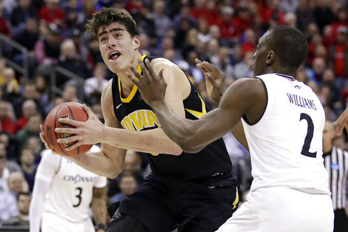 FILE - In this March 22, 2019, file photo, Iowa's Luka Garza (55) drives past Cincinnati's Keith Williams (2) in the second half during a first-round men's college basketball game in the NCAA Tournament in Columbus, Ohio. Returning starters Joe Wieskamp and Luka Garza headline a roster that is deep at every position. (AP Photo/Tony Dejak, File)