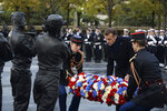 French President Emmanuel Macron lays a wreath of flowers as he inaugurates a memorial for soldiers fallen in foreign conflicts, Monday Nov. 11, 2019 in Paris. As part of commemorations marking 101 years since World War I's Armistice, French President Emmanuel Macron led a ceremony for the 549 French soldiers who died in 17 theaters of conflict since the 60s. The monument memorial depicts six soldiers _ five men and a woman _ holding up an invisible coffin. (Johanna Geron/Pool via AP)