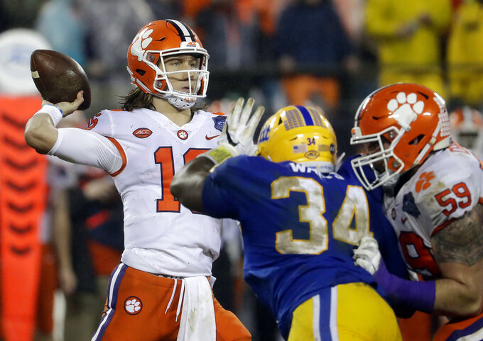 Clemson's Trevor Lawrence (16) looks to pass under pressure from Pittsburgh's Amir Watts (34) in the first half of the Atlantic Coast Conference championship NCAA college football game in Charlotte, N.C., Saturday, Dec. 1, 2018. (AP Photo/Chuck Burton)