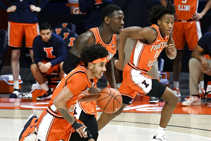 Illinois guard Andre Curbelo (5) center Kofi Cockburn (21) and guard Ayo Dosunmu (11) bring the ball down court against Northwestern in the first half of an NCAA college basketball game Tuesday, Feb. 16, 2021, in Champaign, Ill. (AP Photo/Holly Hart)