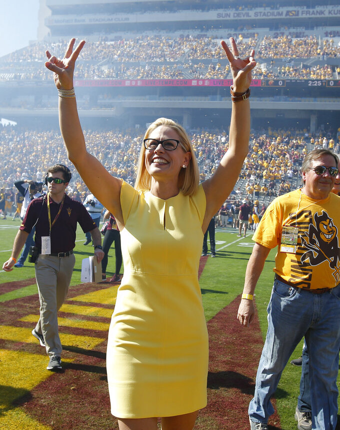 Democratic U.S. Senate candidate Kyrsten Sinema gestures before performing the coin toss before an NCAA college football game between Arizona State and Utah, Saturday, Nov 3, 2018, in Tempe, Ariz. (AP Photo/Rick Scuteri)