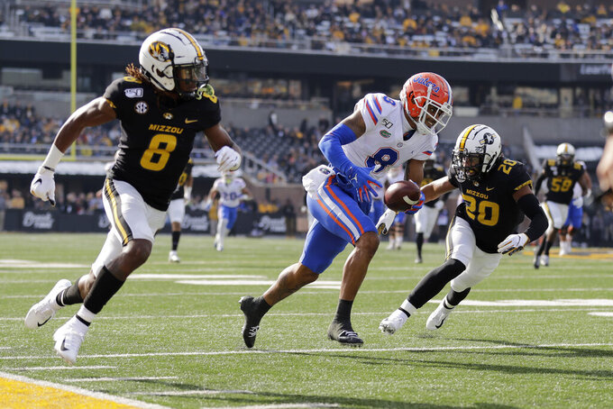 Florida wide receiver Trevon Grimes, center, runs with the ball after catching a pass as Missouri defensive backs Jarvis Ware, left, and Khalil Oliver close in during the first half of an NCAA college football game Saturday, Nov. 16, 2019, in Columbia, Mo. (AP Photo/Jeff Roberson)