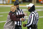 Minnesota head coach P.J. Fleck has a discussion with referee Larry Smith and headline judge William McKoy during a break in action at an NCAA college football game with Michigan Saturday, Oct. 24, 2020, in Minneapolis. (AP Photo/Bruce Kluckhohn)