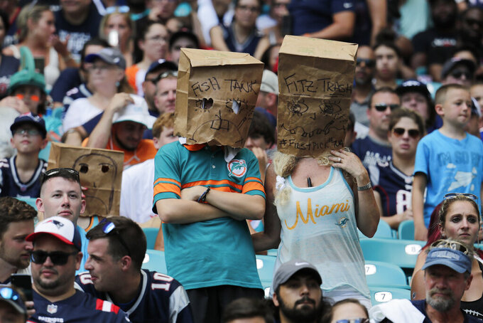 Unhappy Miami Dolphins fans wear paper bags, during the second half at an NFL football game against the New England Patriots, Sunday, Sept. 15, 2019, in Miami Gardens, Fla. The Patriots defeated the Dolphins 43-0. (AP Photo/Lynne Sladky)
