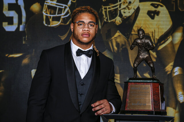 Ohio State defensive end Chase Young poses with the The 2019 Bronko Nagurski Award before the awards banquet in Charlotte, N.C., Monday, Dec. 9, 2019. (AP Photo/Nell Redmond)