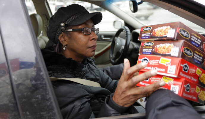 Gayle Bell is handed four free meals courtesy of Stouffer's, Wednesday, Jan. 16, 2019, in Solon, Ohio. Bell has worked for the Department of Treasury for five years. The partial government shutdown has generated an outpouring of generosity to TSA agents and other federal employees who are working without pay. (AP Photo/Tony Dejak)