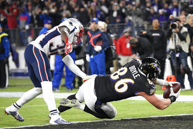 Baltimore Ravens tight end Nick Boyle (86) dives in for a score on a pass from quarterback Lamar Jackson, not visible, as New England Patriots safety Devin McCourty (32) defends during the second half of an NFL football game, Sunday, Nov. 3, 2019, in Baltimore. (AP Photo/Nick Wass)