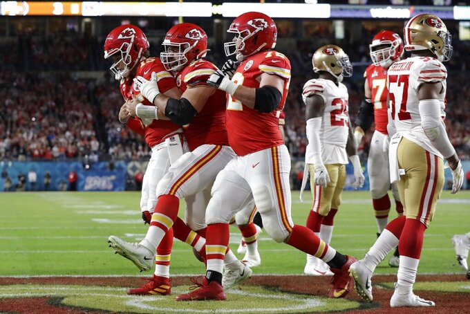Kansas City Chiefs quarterback Patrick Mahomes, left, is congratulated by teamates after scoring against the San Francisco 49ers during the first half of the NFL Super Bowl 54 football game Sunday, Feb. 2, 2020, in Miami Gardens, Fla. (AP Photo/Lynne Sladky)