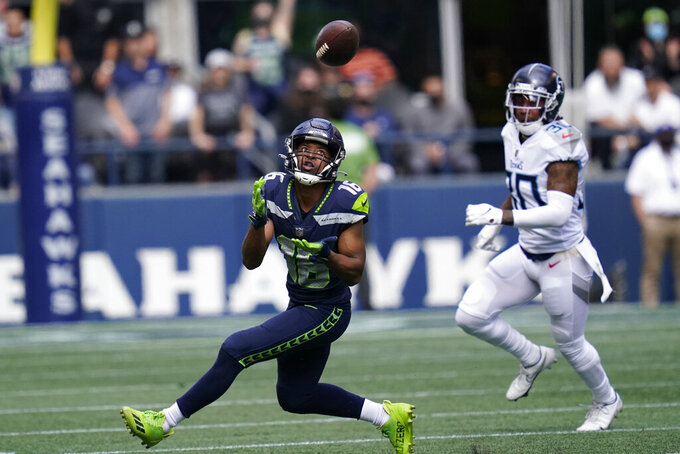 Seattle Seahawks wide receiver Tyler Lockett (16) catches a pass before running for a touchdown in from of Tennessee Titans strong safety Bradley McDougald, right, during the first half of an NFL football game, Sunday, Sept. 19, 2021, in Seattle. (AP Photo/Elaine Thompson)