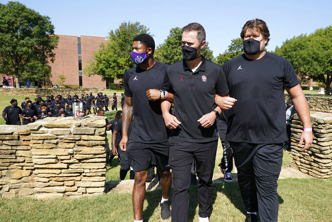 """FILE - Chanse Sylvie, left, head coach Lincoln Riley, center, and Creed Humphrey, right, lead the Oklahoma football team from the Unity Garden after they held a 57-second moment of silence in honor of the 57-year anniversary of the March on Washington and Dr. Martin Luther King, Jr.'s """"I Have a Dream"""" speech, as they protest racial injustice in Norman, Okla., Friday, Aug. 28, 2020. This summer college athletes have organized campus marches, threatened boycotts, and been trending on social media as if they had just scored game-winning touchdowns without stepping foot on a field. (AP Photo/Sue Ogrocki, File)"""