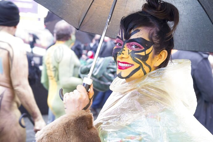 This photo provided by Andy Golub  shows a nude model in a see-through poncho poses with her umbrella in the rain and cold during the Polar Bear Paint body-painting event in New York City's Times Square on Saturday Feb. 10, 2018.  (Andy Golub via AP)