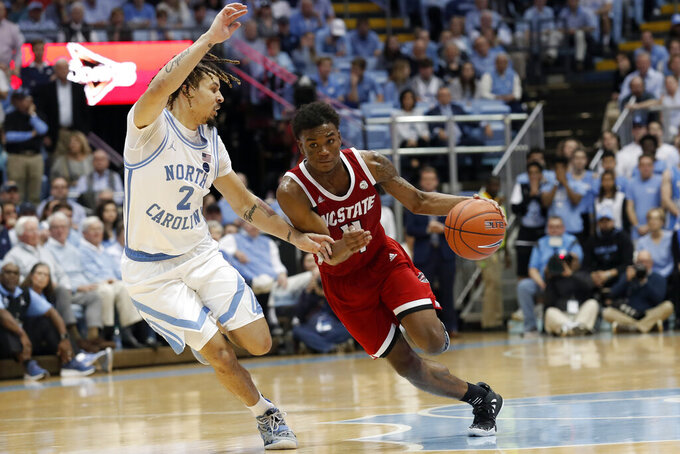 North Carolina guard Cole Anthony (2) defends against North Carolina State guard Markell Johnson (11) during the second half of an NCAA college basketball game in Chapel Hill, N.C., Tuesday, Feb. 25, 2020. (AP Photo/Gerry Broome)