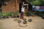 A Sri Lankan Telugu man Masannage Raja lifts a python as he cleans his snakes outside his dwelling in Kalawewa, Sri Lanka, Tuesday, June 16, 2020. Sri Lanka's Telugu community, whose nomadic lifestyle has increasingly clashed with the modern world, is facing another threat that could hasten its decline: the COVID-19 pandemic. (AP Photo/Eranga Jayawardena)