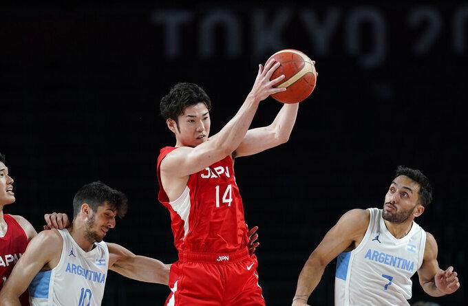 Japan's Kosuke Kanamaru (14) grabs a rebound over Argentina's Facundo Campazzo (7), right, during men's basketball preliminary round game at the 2020 Summer Olympics, Sunday, Aug. 1, 2021, in Saitama, Japan. (AP Photo/Charlie Neibergall)