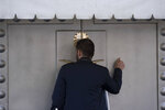 A man knocks the entrance of the Saudi Arabia's consulate in Istanbul, Friday, Oct. 12, 2018. A senior Turkish official says Turkey and Saudi Arabia will form a