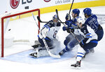 Toronto Maple Leafs left wing Zach Hyman (11) scores past Winnipeg Jets goaltender Connor Hellebuyck (37) as Jets defenseman Dylan DeMelo (2) watches during the first period of an NHL hockey game Tuesday, March 9, 2021, in Toronto. (Nathan Denette/The Canadian Press via AP)