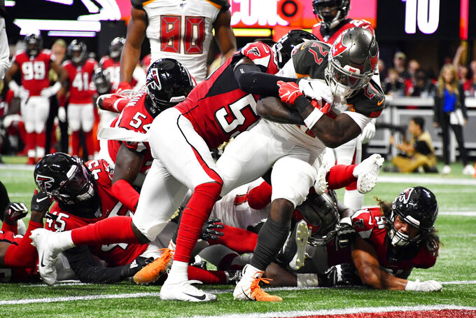 Tampa Bay Buccaneers running back Ronald Jones (27) runs into the end zone for a touchdown against Atlanta Falcons outside linebacker De'Vondre Campbell (59) during the second half of an NFL football game, Sunday, Nov. 24, 2019, in Atlanta. (AP Photo/John Amis)