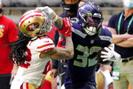 Seattle Seahawks running back Chris Carson (32) stiff arms San Francisco 49ers cornerback Jason Verrett (22) during the first half of an NFL football game, Sunday, Jan. 3, 2021, in Glendale, Ariz. (AP Photo/Rick Scuteri)