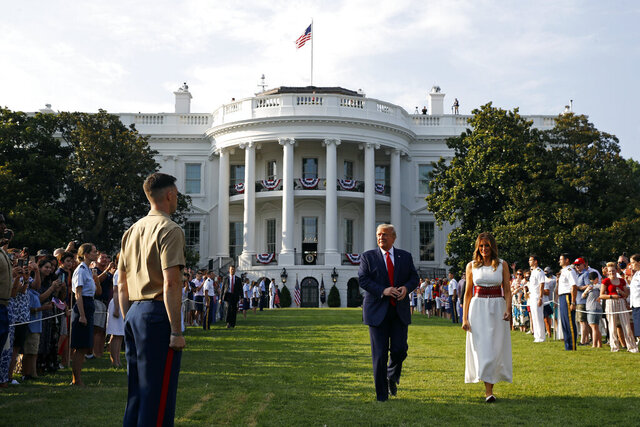 President Donald Trump and first lady Melania Trump walk on the South Lawn of the White House during a
