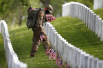 A member of the 3rd U.S. Infantry Regiment also known as The Old Guard, wears a face mask as he places flags in front of each headstone for