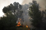 Smoke rises as a wildfire rages near in Kfar Uriya, Thursday, May 23, 2019. Israeli police have ordered the evacuation of several communities in southern and central Israel as wildfires rage amid a major heatwave. (AP Photo/Ariel Schalit)