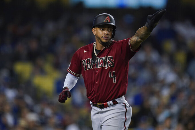 Arizona Diamondbacks' Ketel Marte points to Henry Ramos after scoring off of a single hit by Ramos during the fourth inning of a baseball game against the Los Angeles Dodgers Wednesday, Sept. 15, 2021, in Los Angeles. (AP Photo/Ashley Landis)