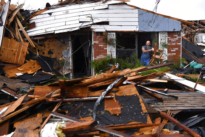 Wesley Mantooth lifts a wooden chair out a window of the home of his father, Robert, in Abilene, Texas, on Saturday, May 18, 2019. Many residents said a tornado struck in the early morning hours. (Ronald W. Erdrich/The Abilene Reporter-News via AP)