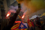 Protesters hold independence flags and flares during the Catalan National Day in Barcelona, Spain, Wednesday, Sept. 11, 2019. The traditional September 11, called
