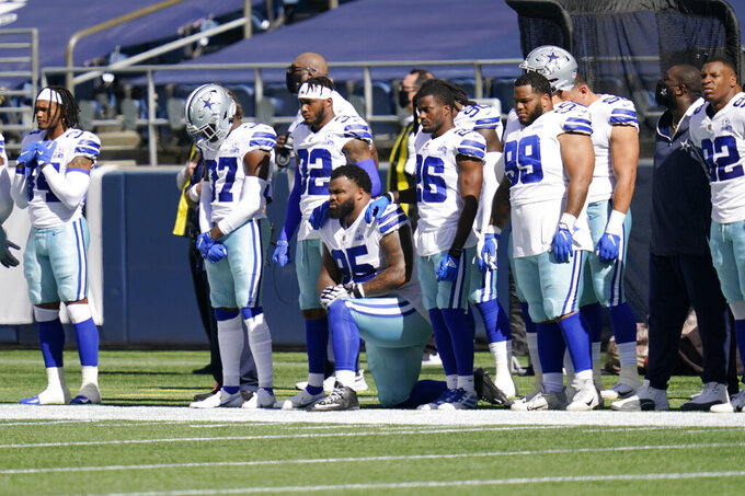 Dallas Cowboys defensive tackle Dontari Poe kneels as teammates stand during the national anthem before an NFL football game against the Seattle Seahawks, Sunday, Sept. 27, 2020, in Seattle. (AP Photo/Elaine Thompson)