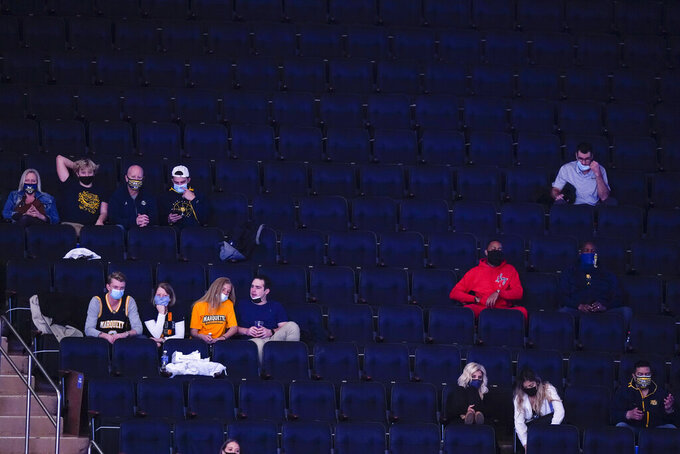 Marquette fans wear protective masks while watching the second half of an NCAA college basketball game against Georgetown in the Big East conference tournament Wednesday, March 10, 2021, in New York. (AP Photo/Frank Franklin II)