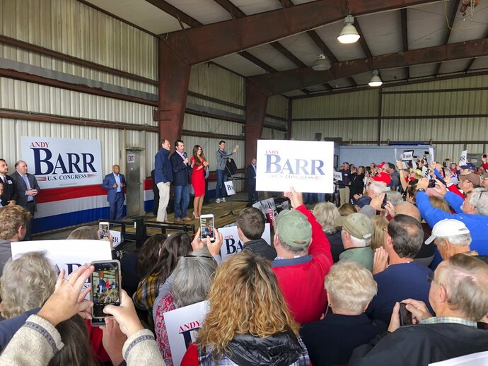 Donald Trump Jr., center, and former Fox News host Kimberly Guilfoyle, right, urge a crowd of supporters to vote for U.S. Rep. Andy Barr, left, at a rally on Monday, Nov. 5, 2018, in Mount Sterling, Ky. Barr is in a tight race for in Kentucky's 6th Congressional district against Democrat Amy McGrath. (AP Photo/Adam Beam)