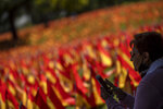 A woman sits near to the Spanish flags placed in memory of coronavirus (COVID-19) victims, in Madrid, Spain, Sunday, Sept. 27, 2020. An association of families of coronavirus victims has planted what it says are 53,000 small Spanish flags in a Madrid park to honor the dead of the pandemic. (AP Photo/Manu Fernandez)