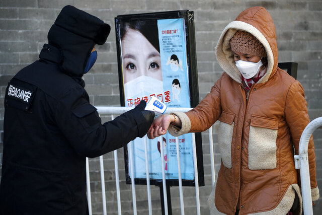 A woman wearing a protective face mask receives a temperature check from a security guard as she enters Qianmen Street, a popular tourist spot, in Beijing, Sunday, Feb. 16, 2020. China reported Sunday a drop in new virus cases for the third straight day, as it became apparent that the country's leadership was aware of the potential gravity of the situation well before the alarm was sounded. (AP Photo/Andy Wong)