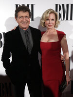 """FILE - Mac Davis and his wife Lise Kristen Gerard appear at the 63rd Annual BMI Country Awards in Nashville, Tenn., on Nov. 3, 2015.  Davis, a country star and Elvis songwriter,   died on Tuesday, Sept. 29, 2020 after heart surgery. He was 78. Davis started his career writing hits for Presley, including """"A Little Less Conversation"""" and """"In the Ghetto."""" The Lubbock, Texas-native had a varied career over the years as a singer, actor and TV host and was inducted into the Songwriters Hall of Fame in 2006. He was named ACM entertainer of the year in 1974 after the success of songs like """"Baby Don't Get Hooked on Me."""" (Photo by Wade Payne/Invision/AP, File)"""