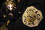 A Chicago police officer shields their candle from the wind as they attend a candlelight vigil for police Cmdr. Paul Bauer outside the Near North District headquarters Wednesday, Feb. 14, 2018, in Chicago. The 53-year-old Bauer, who had been with the department 31 years, was fatally shot as he went to assist other officers who were pursuing the suspect, Shomari Legghette, in downtown Chicago on Tuesday. Legghette is charged with first-degree murder in the shooting of Bauer. (AP Photo/Charles Rex Arbogast)